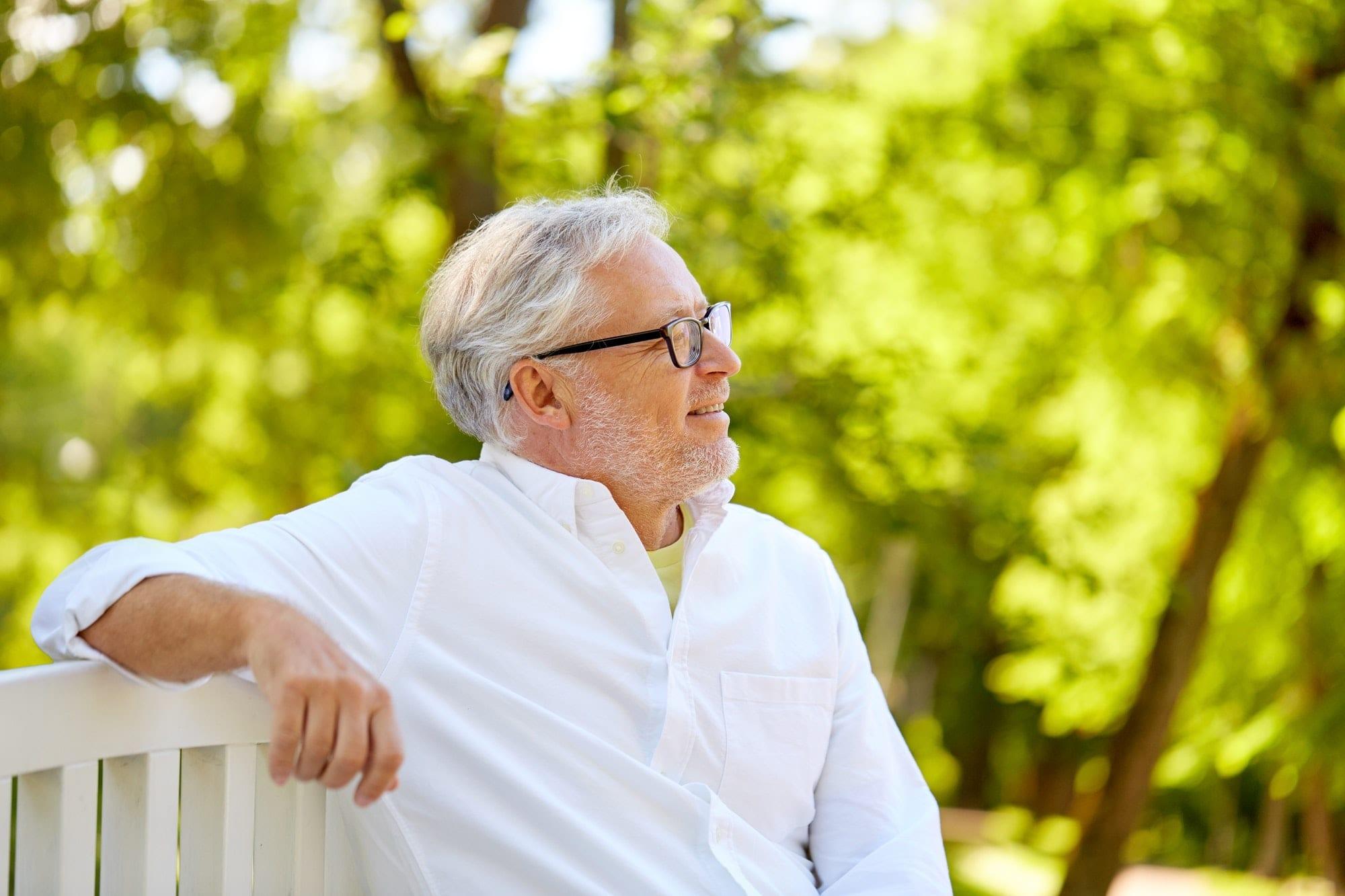 happy senior man in glasses sitting at summer park